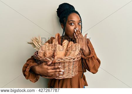 African american woman with braided hair holding wicker basket with bread covering mouth with hand, shocked and afraid for mistake. surprised expression