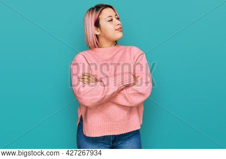 Hispanic woman with pink hair wearing casual winter sweater looking to the side with arms crossed convinced and confident