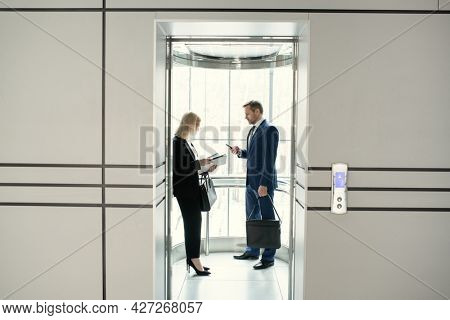 Two business people standing in elevator of modern office building