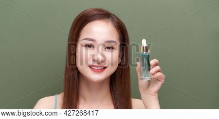 Smiling Woman Holding Vitamin C Serum Near Her Face On Green Background