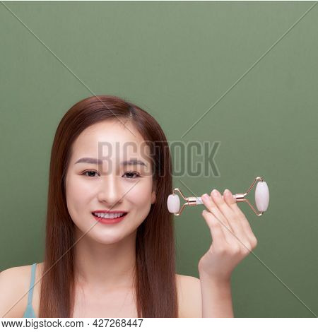 Portrait Photo Of A Young Woman Looking Relaxed Use While Using A Natural Pink Quartz Face Roller