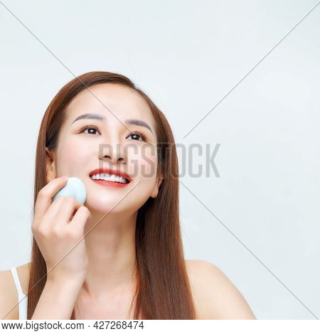 Young Beautiful Woman Applying Cosmetic With Sponge