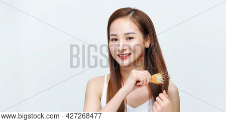 Portrait Of Beautiful Young Woman Combing Her Hair, Looking At Camera And Smiling