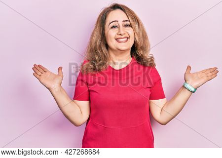 Middle age caucasian woman wearing casual clothes smiling showing both hands open palms, presenting and advertising comparison and balance