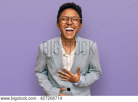 Young african american woman wearing business clothes smiling and laughing hard out loud because funny crazy joke with hands on body.