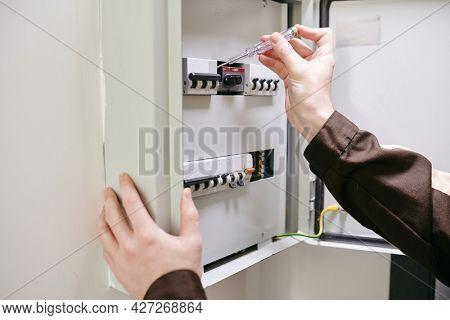 Hands of young electrician using current measuring handtool