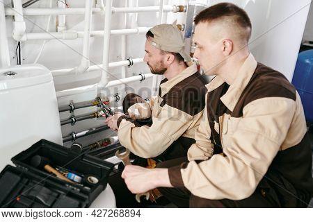 Two young repairmen or plumbers repairing pipes in lavatory