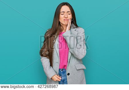 Young hispanic girl wearing business clothes touching mouth with hand with painful expression because of toothache or dental illness on teeth. dentist