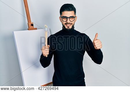 Handsome man with beard holding brushes close to easel stand doing happy thumbs up gesture with hand. approving expression looking at the camera showing success.