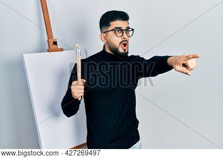 Handsome man with beard holding brushes close to easel stand pointing with finger surprised ahead, open mouth amazed expression, something on the front