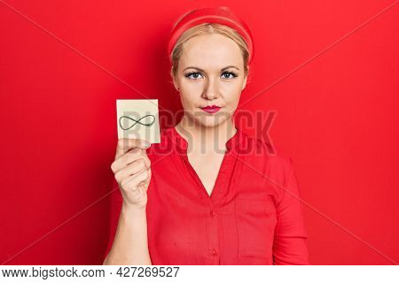 Young blonde woman holding infinite symbol reminder thinking attitude and sober expression looking self confident
