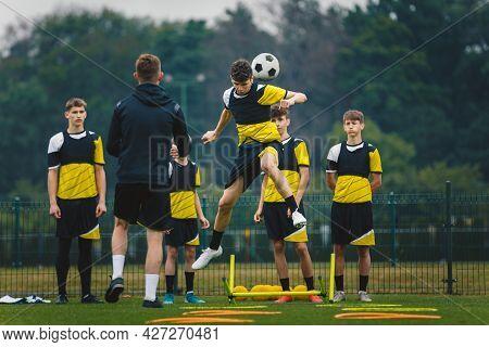 Teenage Football Players Training Headshots  Young Player Jumping High And Head Ball. Coach Coaching