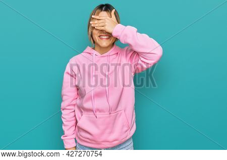Young caucasian woman wearing casual sweatshirt smiling and laughing with hand on face covering eyes for surprise. blind concept.