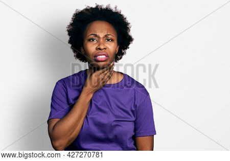 African american woman with afro hair wearing casual purple t shirt touching painful neck, sore throat for flu, clod and infection
