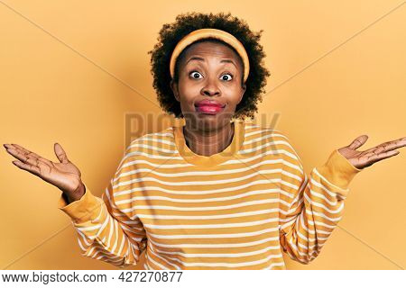 Young african american woman wearing casual sweatshirt clueless and confused with open arms, no idea and doubtful face.