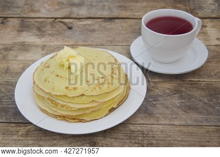 A Large Stack Of Pancakes On A White Plate And Tea On A Wooden, Rustic-style Table. Wooden Breakfast