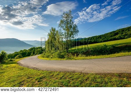 Country Road Down The Hill. Beautiful Travel Background. Sunny Morning Weather In Mountains. Trees A