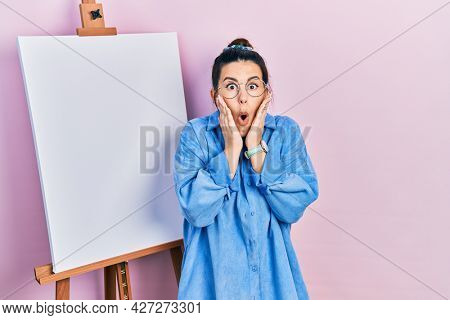 Young hispanic woman standing by painter easel stand afraid and shocked, surprise and amazed expression with hands on face