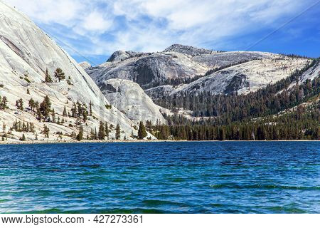 Beautiful Tenaya lake in Yosemite Park, along the Tioga Road. The evergreen forest at the foot of the mountains surrounds the lake. The stone beaches surround the lake