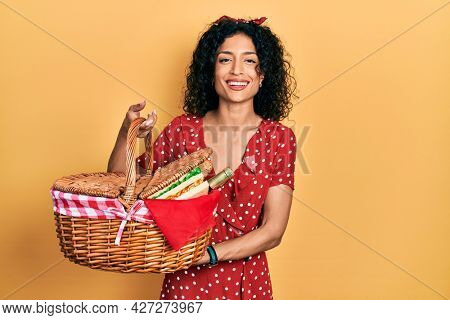 Young latin girl holding picnic wicker basket with bread smiling and laughing hard out loud because funny crazy joke.