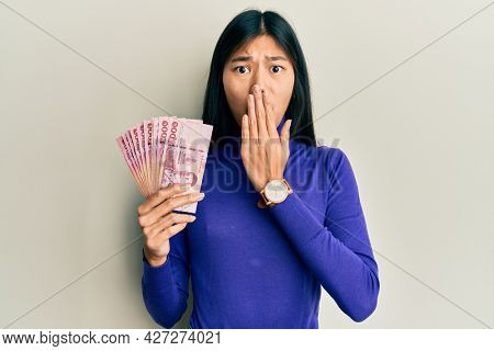 Young chinese woman holding thai baht banknotes covering mouth with hand, shocked and afraid for mistake. surprised expression