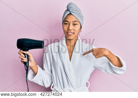 Young woman wearing shower towel cap and bathrobe holding dryer pointing finger to one self smiling happy and proud