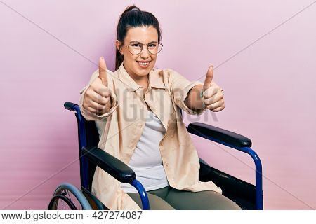 Young hispanic woman sitting on wheelchair approving doing positive gesture with hand, thumbs up smiling and happy for success. winner gesture.