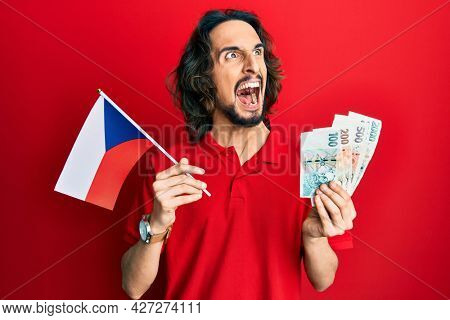 Young hispanic man holding czech republic flag and koruna banknotes angry and mad screaming frustrated and furious, shouting with anger. rage and aggressive concept.