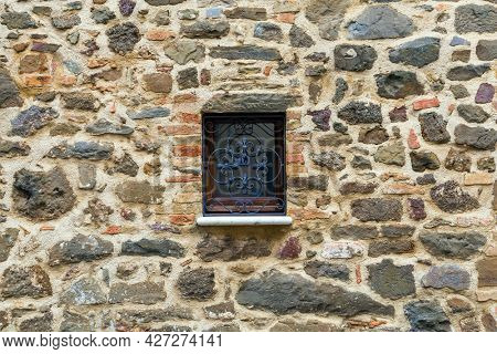 Cloudy autumn day in Tuscany. The small town of Montalcino. The beautiful decor element of a small window - metal window grill. The concept of cognitive, active and photo tourism