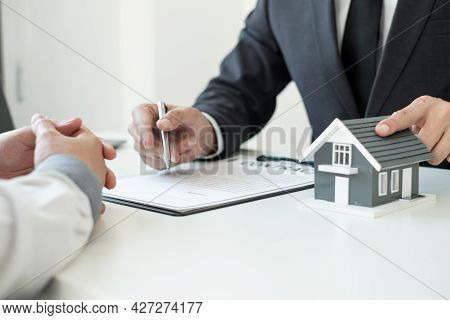 A Real Estate Agent With A House Model Is Talking To Clients About Buying Home Insurance. Real Estat