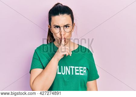 Young hispanic woman wearing volunteer t shirt asking to be quiet with finger on lips. silence and secret concept.