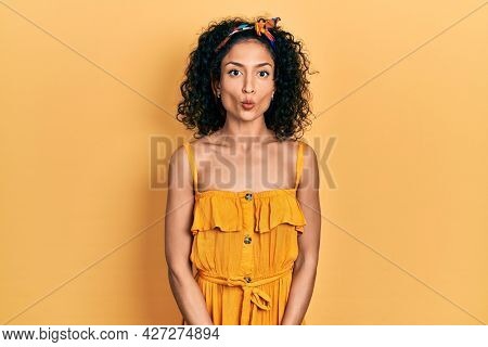 Young latin girl wearing summer dress making fish face with lips, crazy and comical gesture. funny expression.