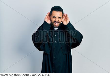 Handsome hispanic man with beard wearing catholic priest robe trying to hear both hands on ear gesture, curious for gossip. hearing problem, deaf
