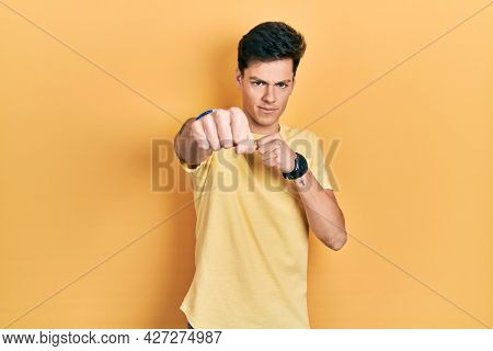 Young hispanic man wearing casual yellow t shirt punching fist to fight, aggressive and angry attack, threat and violence