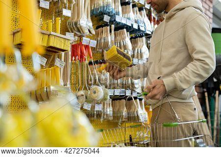 Man in hoodie choosing brush in household department or hardware store