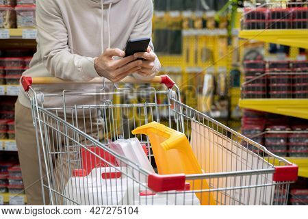 Young man scrolling in smartphone over shopping cart with household goods