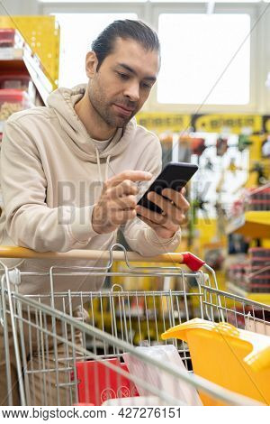 Male consumer with smartphone and shopping cart full of household goods