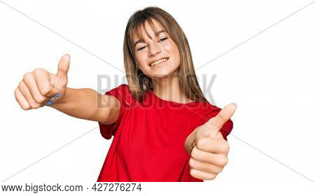 Teenager caucasian girl wearing casual red t shirt approving doing positive gesture with hand, thumbs up smiling and happy for success. winner gesture.