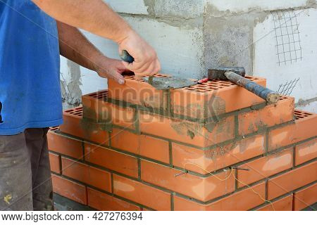 Masonry Brickwork. A Masonry Contractor Is Laying The House Corner With Face Bricks Bonding Them Wit
