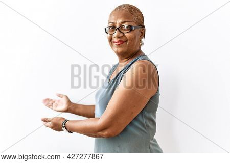 Mature hispanic woman wearing glasses standing over isolated background inviting to enter smiling natural with open hand
