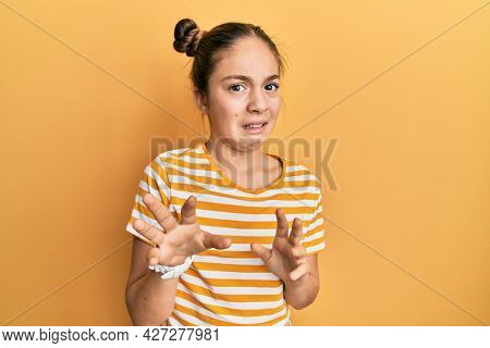 Beautiful brunette little girl wearing casual striped t shirt disgusted expression, displeased and fearful doing disgust face because aversion reaction.