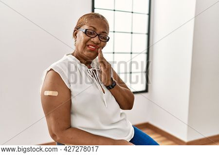 Mature hispanic woman getting vaccine showing arm with band aid touching mouth with hand with painful expression because of toothache or dental illness on teeth. dentist concept.