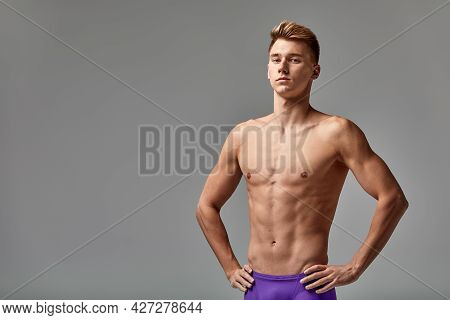 Young Swimmer In Excellent Physical Shape, On A Gray Background With Copy Space, Call For Sports, Ad