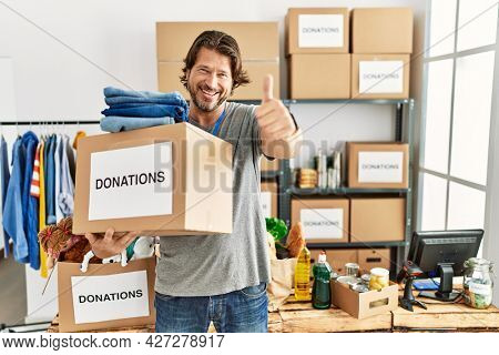 Handsome middle age man holding donations box for charity at volunteer stand approving doing positive gesture with hand, thumbs up smiling and happy for success. winner gesture.