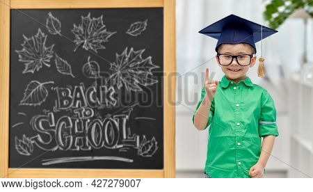education, learning and people concept - happy little student boy in bachelor hat or mortarboard and eyeglasses pointing finger up over chalkboard with back to school lettering on background