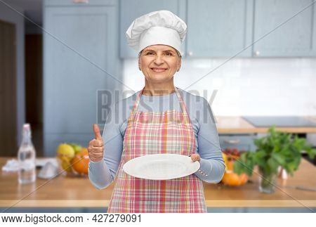 cooking, culinary and old people concept - portrait of smiling senior woman or chef in toque in apron holding empty plate showing thumbs up over home kitchen background