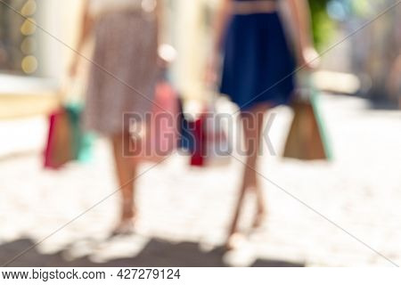 sale, consumerism and people concept - blurred picture of young women with shopping bags walking along city street