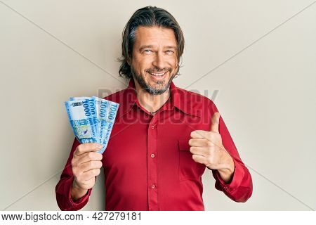 Middle age handsome man holding 1000 hungarian forint banknotes smiling happy and positive, thumb up doing excellent and approval sign