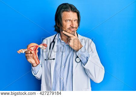 Middle age handsome gynecologist man holding anatomical model of female genital organ serious face thinking about question with hand on chin, thoughtful about confusing idea