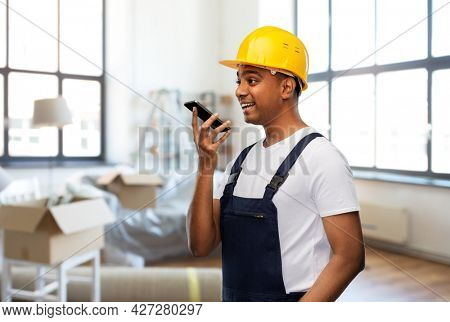 moving, repair and people concept - happy smiling indian worker, loader or repairman in helmet using voice command recorder on smartphone over new home background